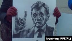 Учасниця мітингу з плакатом, яка вимагає відставки «губернатора» Сергія Меняйла