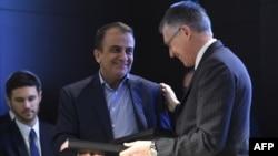 هشام یکهزارع (سمت چپ) در حال مبادله اسناد همکاری با مدیرعامل شرکت پژو در سال ۱۳۹۵.