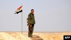 Сирийский военный на фоне флага.