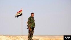 Сирийский военный на фоне флага