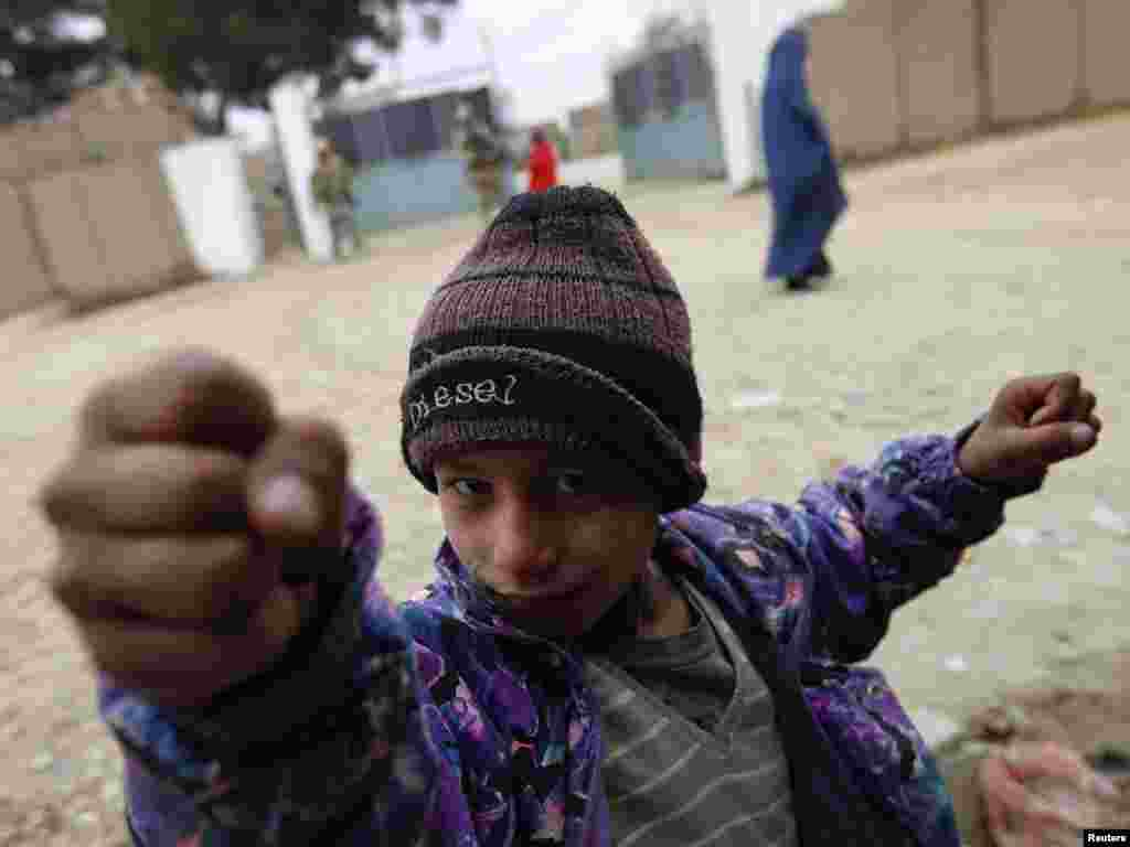An Afghan boy gestures in front of an international combat outpost in Iman Sahib, Afghanistan. Photo by Fabrizio Bensch for Reuters