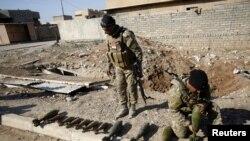 Сотрудники иракских сил безопасности перед оружием, собранным после изгнания боевиков ИГ из Талкифа, района к северу от Мосула. 20 января 2017 года.