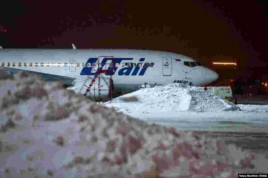Самолет авиакомпании Utair в аэропорту Внуково во время снегопада.