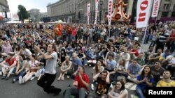 Soccer fans react as they watch the soccer match between the Netherlands and Denmark in the fan zone in Kyiv