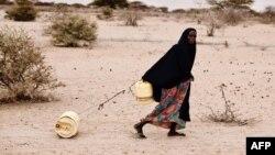 Kenyalı qadın ailəsinə su daşıyır.