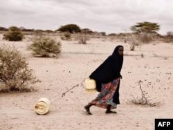 Женщина катит по пустыне контейнер с водой для своей семьи. Засуха в Эфиопии, 2011 год