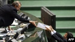 President Mahmud Ahmadinejad (right) handed over his draft annual budget to lawmakers on January 24.