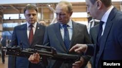 Президент России Владимир Путин держит в руках оружие во время посещения оружейного завода в Туле. 20 января 2014 года.