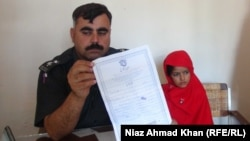 A police officer and a 6-year-old bride in Swat, in northwestern Pakistan, in a photo from a separate case from late October.