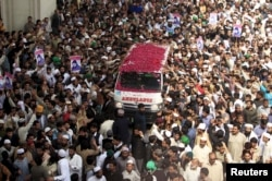 Qadri supporters shower rose petals on an ambulance carrying his body on March 1.