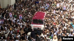 Supporters of Mumtaz Qadri shower rose pastels on an ambulance carrying his body for funeral in Rawalpindi, on March 1