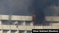 Мужчина пытается спуститься с балкона в здании отеля «Интерконтиненталь» во время вооруженной атаки. Кабул, 21 января 2018 года.