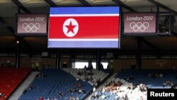 Spectators sit in the stands under the proper North Korean national flag ahead of their women's Group G football match against Colombia.