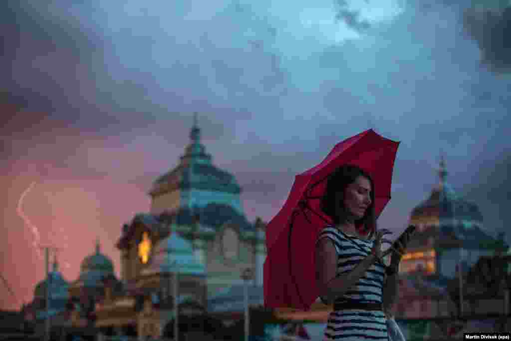 A woman holds an umbrella while using her mobile phone as a lightning storm rolls into Prague, in the Czech Republic. (epa/Martin Divisek)