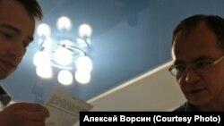 Сотрудник военкомата вручает кандидату в мэры Хабаровска Алексею Ворсину повестку
