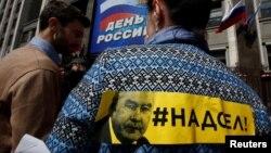 Портрет Собянина на плакате, размещенном на спине женщины, Москва, 9 июня 2017 года