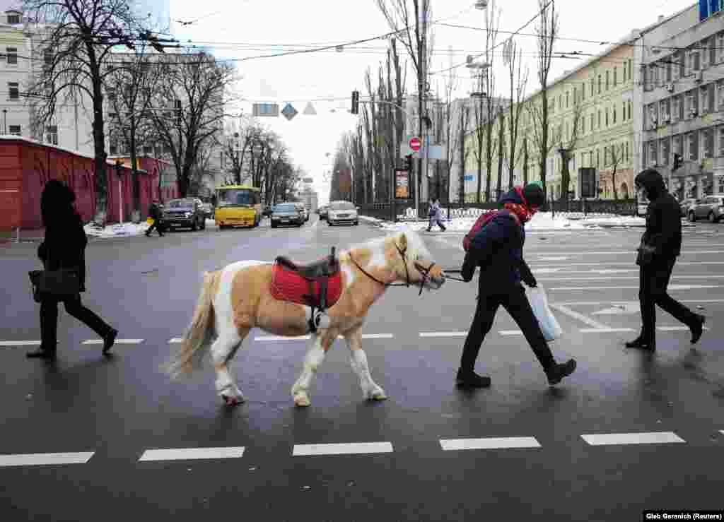 A man with a pony walks on a pedestrian crossing in central Kyiv. (Reuters/Gleb Garanich)