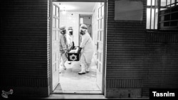 Workers in Iran carry the body of a coronavirus victim to morgue to prepare it for burial. April 6, 2020.