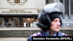 Співробітник МВС біля будівлі кримського парламенту в Сімферополі, який захопили «невідомі озброєні люди», 27 лютого 2014 року