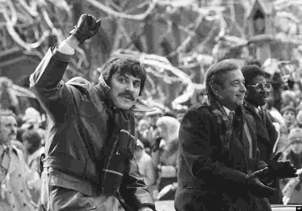 Бывший заложник Алан Голачински из Мэриленда, машет рукой во время парада на Манхэттене, посвященного возвращению американцев. 30 января 1981 года. Соглашение, которое привело к освобождению заложников, предусматривало размораживание 7,9 миллиарда долларов иранских активов за рубежом. Заложникам не дали возможности подать в суд на Иран, но в 2015 году правительство США предоставило им по 4,4 миллиона долларов США. Деньги были взяты с штрафа в размере 8,9 миллиарда долларов, взысканного с французского банка BNP Paribas за причастность к нарушению экономических санкций против Ирана.
