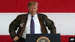 Американскиот претседател Доналд Трамп облекува пилотска јакна за време на средбата со американските војници во воздухопловната база Јокота во близина на Токио