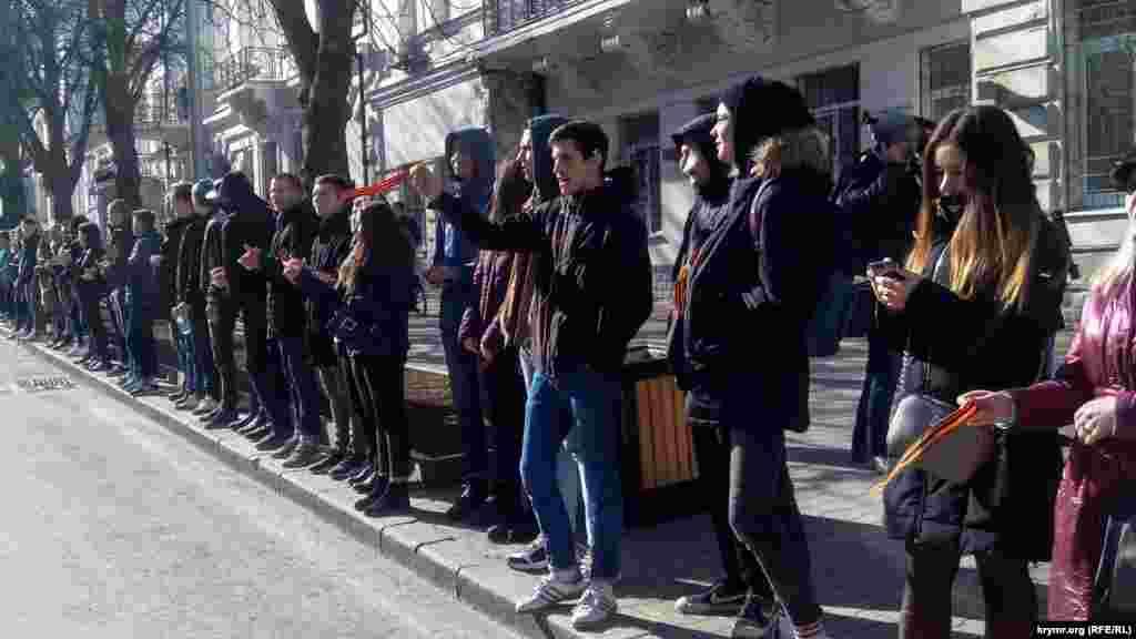 Школярі з російськими прапорцями і «георгіївськими стрічками» вітають колону учасників урочистого мітингу