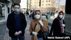 Residents in Tehran, Iran's capital, walk downtown wearing masks and gloves on February 27, 2020.