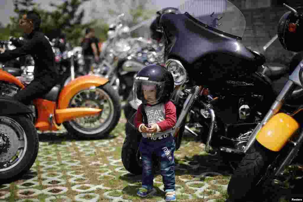 Хлопчык побач з матацыклам Harley Davidson падчас штогадовага ралі Harley Davidson у Кітаі.