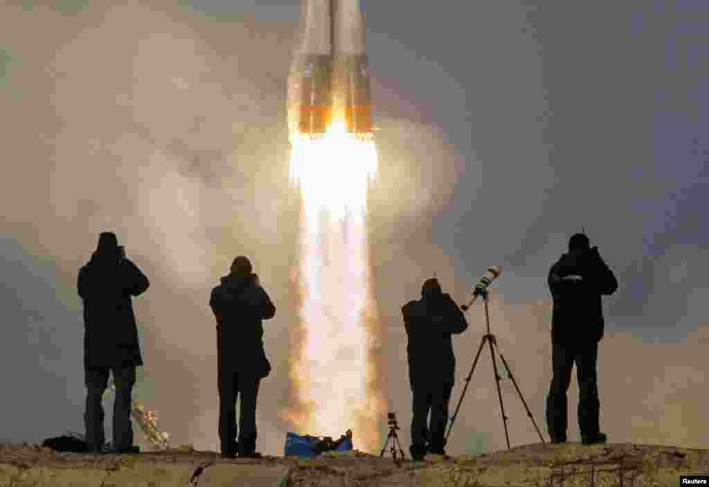 Photographers take pictures of the Soyuz TMA-19M spacecraft carrying the crew of Timothy Peake of Britain, Yuri Malenchenko of Russia and Timothy Kopra of the United States. The crew was en route to the International Space Station (ISS) from the launchpad at the Baikonur Cosmodrome in Kazakhstan, on December 15, 2015. (Reuters/Shamil Zhumatov)