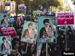 Ирандык руханий көсөмү Аятолла Али Хаменейинин портреттерин көтөргөн аялдар АКШнын Тегерандагы мурдакы элчиканасы алдындагы анти-америкалык демонстрацияда. 4-ноябрь, 2011