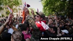 A soldier who has joined protests in Yerevan is carried above the crowd after being given a red rose.