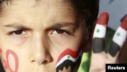 Мальчик с нарисованным сирийским флагом на пальцах протестует против президента Сирии Башара Асада. Амман, Иордания, 12 июня 2011 года.