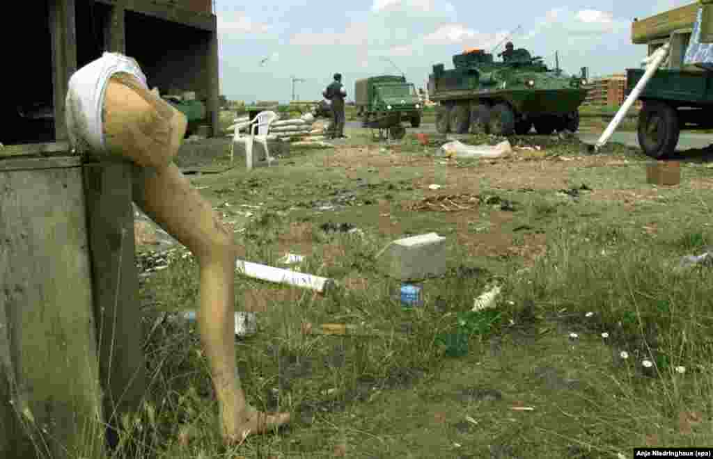 Parts of a plastic mannequin stand next to a destroyed house on the outskirts of Glogovac, 35 kilometers west of Pristina, on June 17, 1999, while NATO vehicles drive through the area.