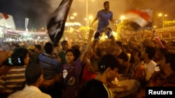 Egypt -- Members of Ultras, hardcore supporters of ousted Egyptian President Mohamed Mursi, shout slogans and wave flags around Cairo University and Nahdet Misr Square where they are camping in Giza, south of Cairo August 2, 2013.