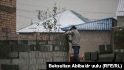 Бишкекчанин строит забор для своего дома. Иллюстративное фото.