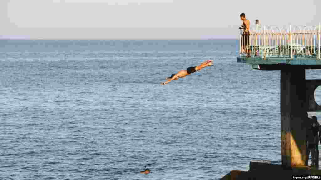 Бесстрашный молодой человек ныряет в море с высоты в несколько метров