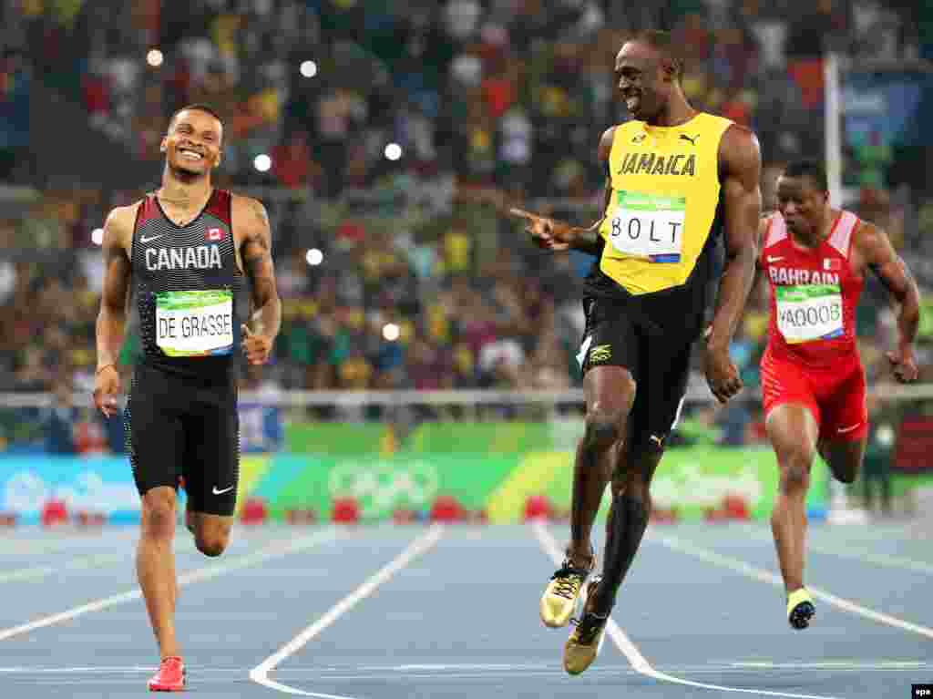 Andre de Grasse (left) of Canada and Usain Bolt of Jamaica react after competing during the men's 200-meter semifinals.