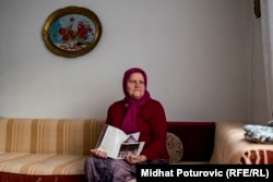 Dzejma Pasic holds a letter and photos of her children; her two sons were killed in what was ruled by a UN international court to have been genocide.