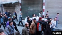 """Несколько человек несут тело повстанца, убитого, по их словам, в столкновениях с бойцами группировки """"Исламское государство в Сирии и Леванте"""""""