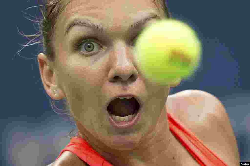 Simona Halep of Romania watches the ball as she returns a shot to Victoria Azarenka of Belarus during their quarterfinals match at the U.S. Open Championships tennis tournament in New York. Halep won 6-3, 4-6, 6-4. (Reuters/Carlo Allegri)