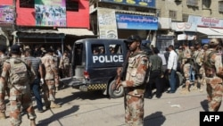 Pakistan -- Pakistani security personnel gather around a police van after an attack by gunmen on security members guarding a polio vaccination team in Karachi, April 20, 2016