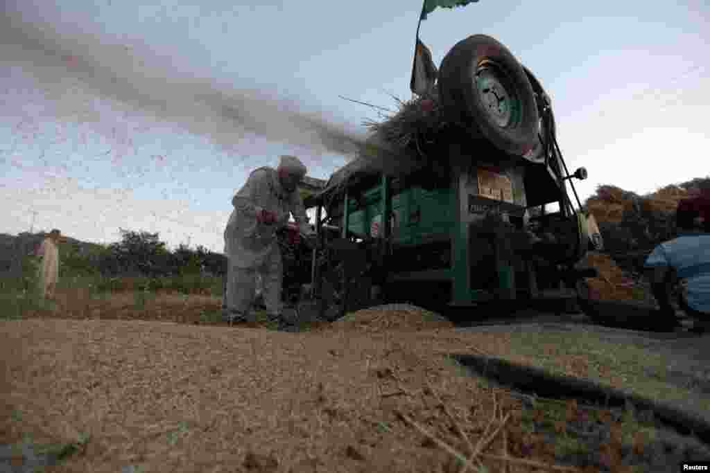 A man works on a wheat thresher in a field in the outskirts of Islamabad, Pakistan.