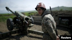 An ethnic Armenian soldier stands next to a cannon at artillery positions near Nagorno-Karabakh's town of Martuni.