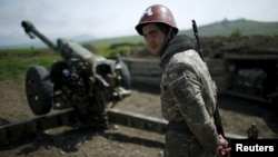 Nagorno-Karabakh -- An ethnic Armenian soldier stands next to a cannon at the artillery positions near Nagorno-Karabakh's town of Martuni, April 8, 2016
