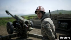 Nagorno-Karabakh -- An Armenian soldier stands next to a cannon at the artillery positions near Nagorno-Karabakh's town of Martuni, April 8, 2016