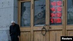 Мужчина у пункта обмена валют в Москве.