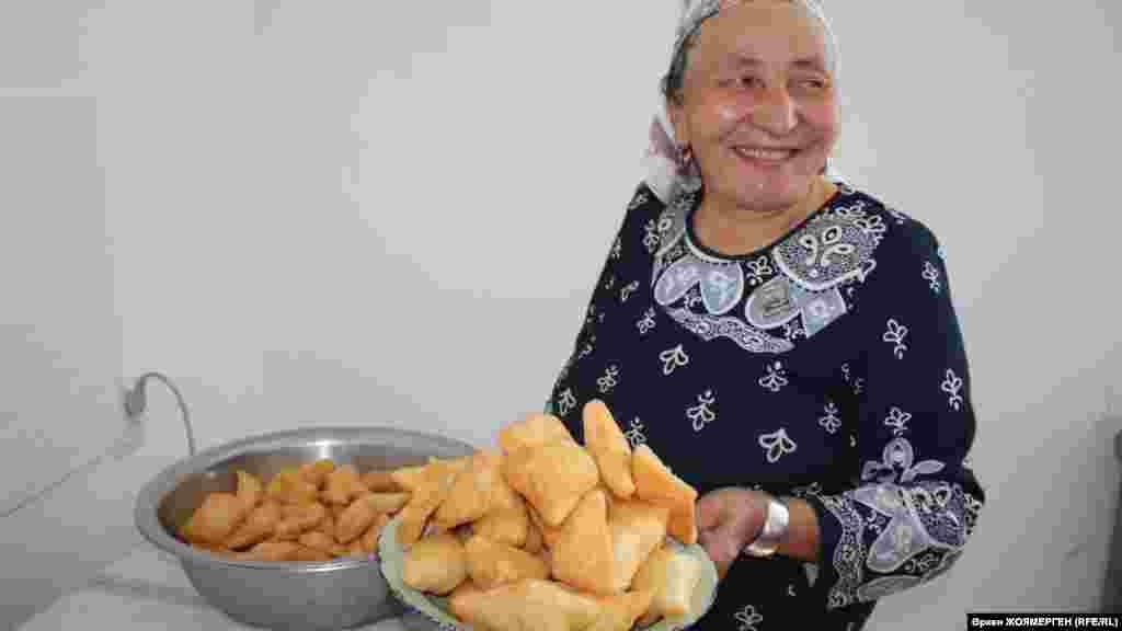 Его жена несет национальное угощение— бауырсак.