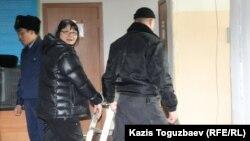 Редактораоппозиционного сайта Nakanune.kz Гузяль Байдалинову (в центре) ведут в зал заседания суда в наручниках. Алматы, 26 декабря 2015 года.
