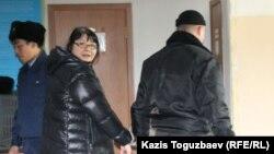 Редактора оппозиционного сайта Nakanune.kz Гузяль Байдалинову (в центре) ведут в зал заседания суда в наручниках. Алматы, 26 декабря 2015 года.