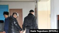 Полицейский уводит Гузяль Байдалинову, редактора сайта Nakanune.kz, после решения суда об аресте. Алматы, 26 декабря 2015 года.
